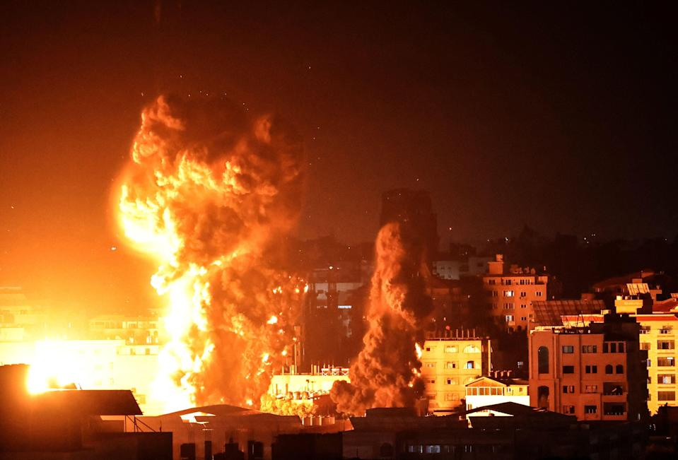 Fire and smoke rise above buildings in Gaza City as Israeli warplanes target the Palestinian enclave early on MondayAFP via Getty Images