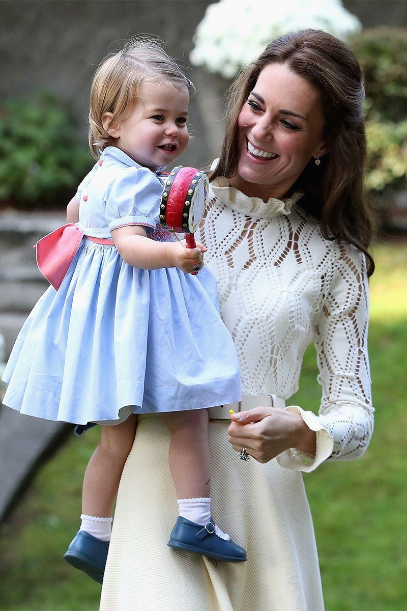<p>The Duchess of Cambridge holds Princess Charlotte as she plays with a toy tambourine.</p>
