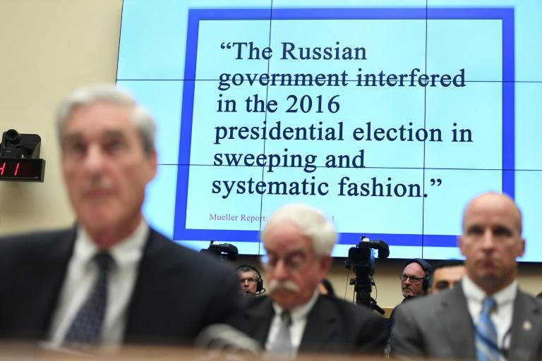 Former special counsel Robert Mueller testifies before Congress in front of a quote from his final report on the investigation into Russian election interference in the 2016 election (AFP Photo/SAUL LOEB)