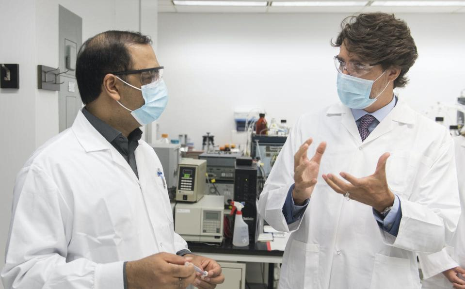 """<span class=""""caption"""">Prime Minister Justin Trudeau, right, speaks with scientist Krishnaraj Tiwari at the National Research Council of Canada (NRC) Royalmount Human Health Therapeutics Research Centre facility in Montreal, Aug 31, 2020</span> <span class=""""attribution""""><span class=""""source"""">THE CANADIAN PRESS/Graham Hughes</span></span>"""