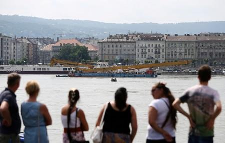 People watch a crane near the site of a tourist boat accident in the Danube river in Budapest