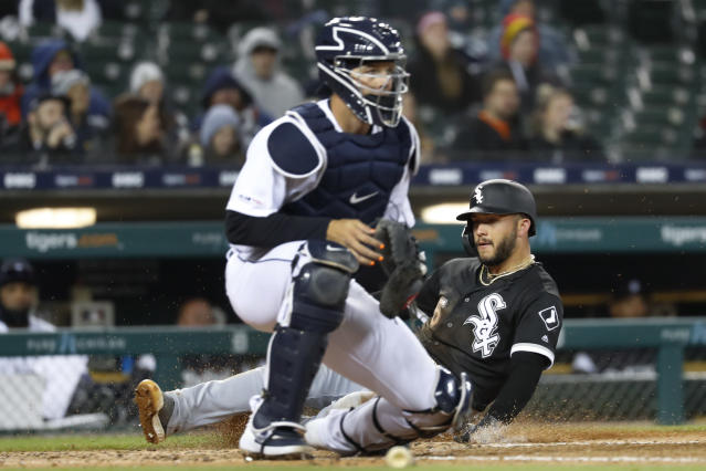 Chicago White Sox's Yolmer Sanchez (5) sides home to score next to Detroit Tigers catcher Grayson Greiner during the seventh inning of a baseball game in Detroit, Friday, April 19, 2019. (AP Photo/Paul Sancya)