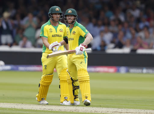 Australia's David Warner, right celebrates with teammate Australia's captain Aaron Finch after getting 50 runs not out during their Cricket World Cup match between England and Australia at Lord's cricket ground in London, Tuesday, June 25, 2019. (AP Photo/Alastair Grant)