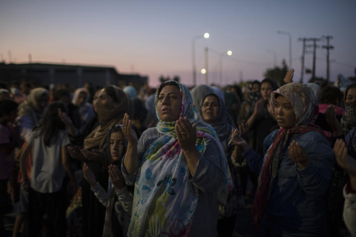 FILE - In this Sunday, Sept. 13, 2020, file photo refugee and migrant women from the destroyed Moria camp pray on the road that are sheltered, in Lesbos island, Greece. Greece's notoriously squalid refugee camp of Moria burnt down last September on the island of Lesbos. It left around 12,000 people in need of emergency housing as winter approached. European leaders then vowed such squalid facilities would be a thing of the past. But aid agencies say that a year later the conditions for asylum seekers on the eastern Greek islands have barely improved. (AP Photo/Petros Giannakouris, File)