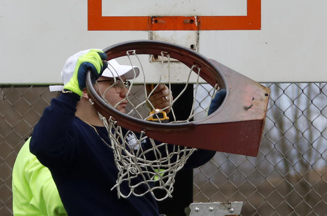 A Pittsburgh public works employee removes a basketball rim from a court Monday because people were not following social distancing rules while using the courts during the weekend. (AP Photo/Gene J. Puskar)