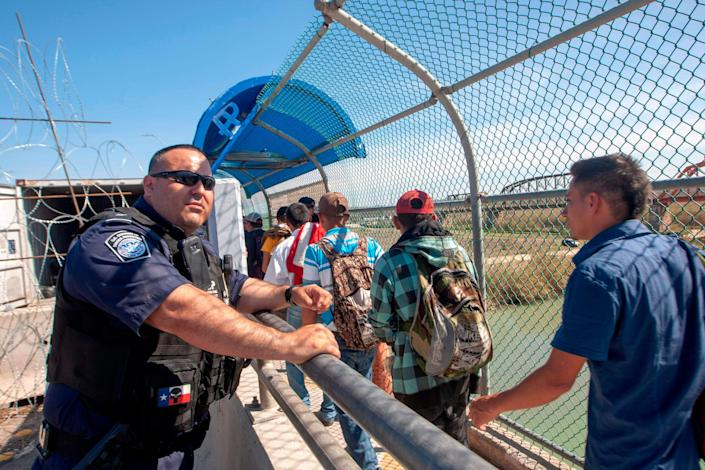 """16 Central American migrants cross the International Bridge II to be interviewed by U.S. immigration authorities and have the possibility of receiving asylum, in Piedras Negras, Coahuila state, Mexico, on the border with the US, on February 16, 2019. - Some 50 Central American migrants staying at a shelter in Piedras Negras, have already been accepted to begin their application for political asylum in the United States. President Donald Trump, repeating his claim that """"walls work,"""" announced Friday that he will declare a national emergency in order to build a barrier on the US-Mexico border without funding from Congress. (Photo by Julio Cesar AGUILAR / AFP)"""
