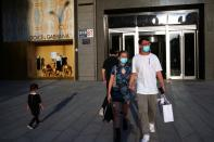 People wearing face masks following the COVID-19 outbreak walk out of a shopping mall in Beijing