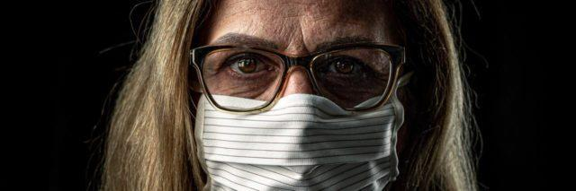 photo of older woman with glasses and blonde hair, standing in darkness and wearing a white face mask to protect against coronavirus
