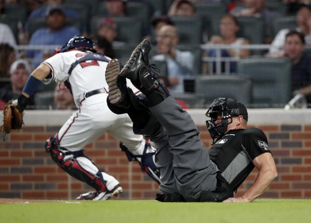 Umpire Jim Wolf (28) falls as he collides with Atlanta Braves catcher Kurt Suzuki (24), background, who was chasing a dropped third strike in the fourth a inning of a baseball game against the Chicago Cubs, Tuesday, May 15, 2018, in Atlanta. A run scored. (AP Photo/John Bazemore)
