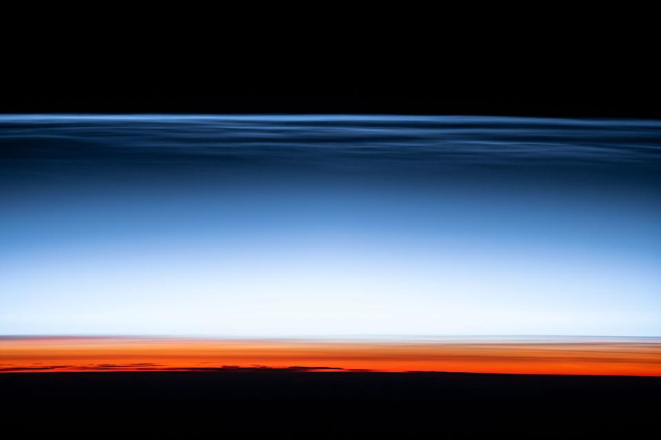 "An astronaut at the International Space Station captured this image of noctilucent or ""night-shining"" clouds in Earth's upper atmosphere. These clouds, which are made of tiny ice crystals, are only visible during astronomical twilight, when the sun just below the horizon, but the clouds are still illuminated by sunlight. Below the blue cloud layer, the lower part of the atmosphere glows with the signature reddish color of sunset."