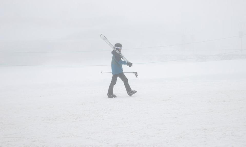 Skiers return to the carpark after fresh snowfalls and a complete white out at Perisher ski fields