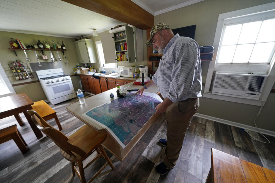 CEO and president Harold Osborn, great-great-grandson of the McIlhenny Co.'s founder, looks at a map of the company's land and surrounding area, inside an old trapper's camp that has been restored and repurposed by the company, on Avery Island, La., where Tabasco brand pepper sauce is made, Tuesday, April 27, 2021. (AP Photo/Gerald Herbert)