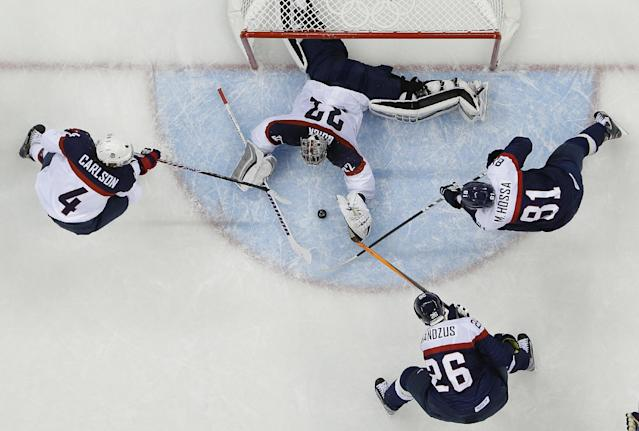 USA goaltender Jonathan Quick (32) reaches for Slovakia forward Michal Handzus's (26) shot at the goal as Slovakia forward Marian Hossa (81) adds pressure to the play and USA defenseman John Carlson (4) helps defend the goal during the 2014 Winter Olympics men's ice hockey game at Shayba Arena, Thursday, Feb. 13, 2014, in Sochi, Russia. USA defeated Slovakia 7-1. (AP Photo/Matt Slocum)