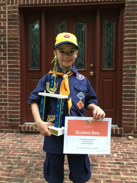 Boy posing with Scout trophy and Scout certificate