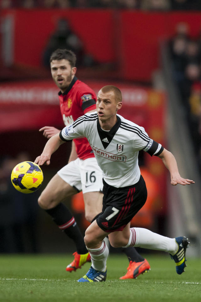 Fulham's Steve Sidwell, foreground, keeps the ball from Manchester United's Michael Carrick during their English Premier League soccer match at Old Trafford Stadium, Manchester, England, Sunday Feb. 9, 2014. (AP Photo/Jon Super)