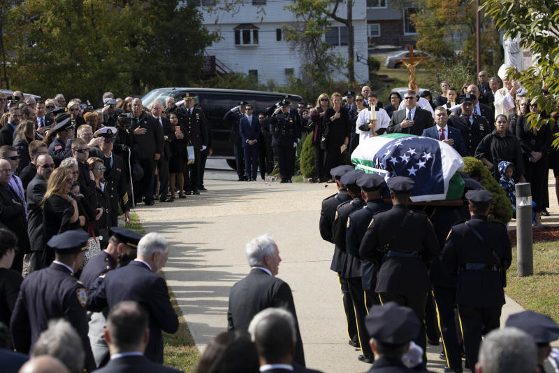 The casket bearing New York City Police Officer Brian Mulkeen is carried into Church of the Sacred Heart, Friday, Oct. 4, 2019, in Monroe, N.Y. Authorities say Mulkeen was fatally hit Sunday by two police bullets while struggling with an armed man in the Bronx. He is the second New York City officer killed by friendly fire this year. (AP Photo/Mark Lennihan)