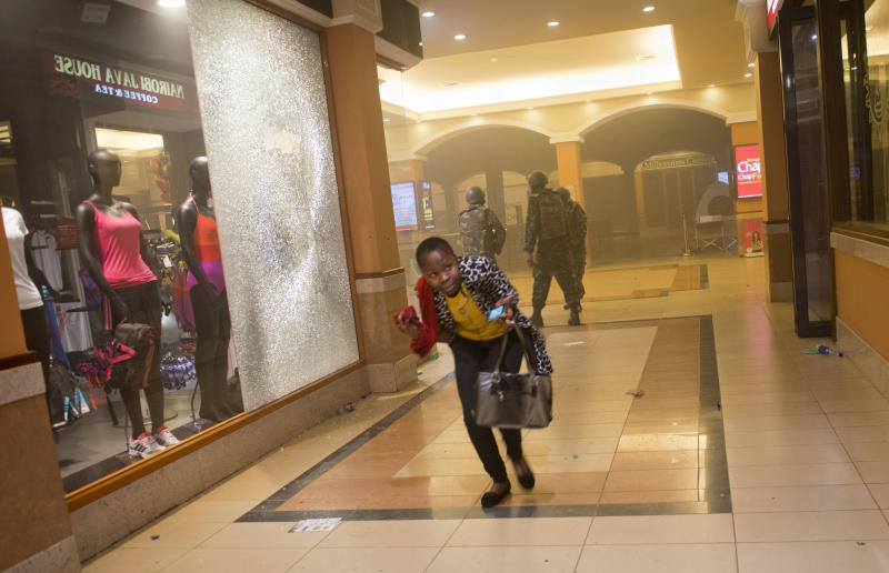 FILE - In this Saturday, Sept. 21, 2013 file photo, a woman who had been hiding during the gun battle runs for cover after armed police enter the Westgate Mall in Nairobi, Kenya, after gunmen threw grenades and opened fire. Security officials in Kenya said Monday, Nov. 11, 2013 that a Westgate Mall attacker whom they named as Mohammed Abdinur Said once lived in the Kakuma refugee camp in northwestern Kenya that houses more than 54,000 Somali refugees. (AP Photo/Jonathan Kalan, File)