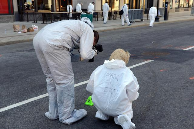 BOSTON, MA - APRIL 17: FBI crime scene investigators photograph evidence after placing a marker on Boylston Street just past Berkeley Street April 17, 2013 in Boston, Massachusetts. Investigators continue to work the scene of two bomb explosions at the finish line of the marathon that killed 3 people and injured over one hundred more. (Photo by Darren McCollester/Getty Images)