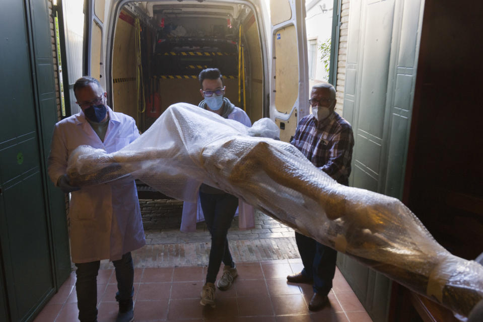 A restored figure of Jesus arrives into Nuestra Senora de la Candelaria church in Seville, southern Spain, Thursday, March 25, 2021. Few Catholics in devout southern Spain would have imagined an April without the pomp and ceremony of Holy Week processions. With the coronavirus pandemic unremitting, they will miss them for a second year. (AP Photo/Laura Leon)