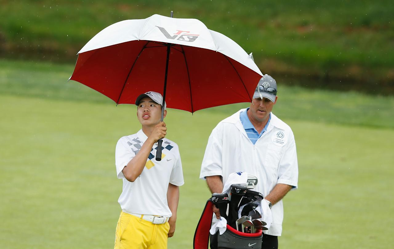 DUBLIN, OH - MAY 31: Guan Tianlang of China waits with his caddie on the 18th hole during the second round of the Memorial Tournament presented by Nationwide Insurance at Muirfield Village Golf Club on May 31, 2013 in Dublin, Ohio. (Photo by Scott Halleran/Getty Images)