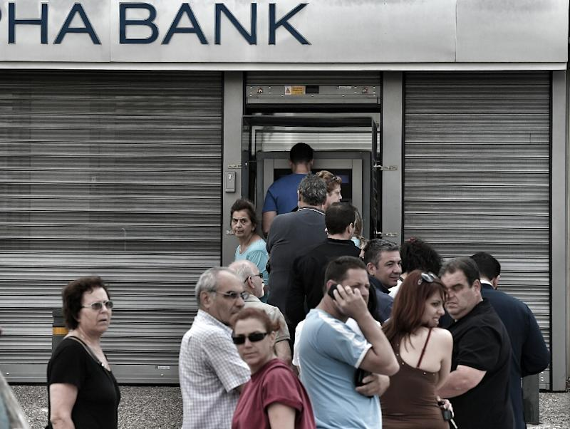 People stand in a queue to use ATM machines to withdraw cash at a bank in Athens on June 27, 2015
