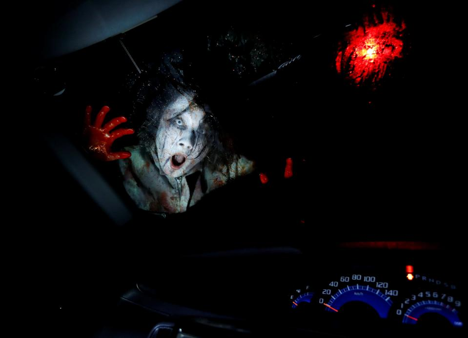 An actor dressed as a zombie performs during a drive-in haunted house show, performed by Kowagarasetai (Scare Squad), for people inside a car in order to maintain social distancing amid the spread of the coronavirus disease (COVID-19), at a garage in Tokyo, Japan July 3, 2020.  REUTERS/Issei Kato     TPX IMAGES OF THE DAY