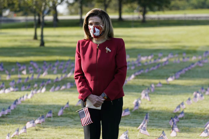 House Speaker Nancy Pelosi pauses and looks at small flags placed on the grounds of the National Mall by activists from the COVID Memorial Project to mark the deaths of 200,000 lives lost in the U.S. to COVID-19, Tuesday, Sept. 22, 2020 in Washington. (AP Photo/J. Scott Applewhite)