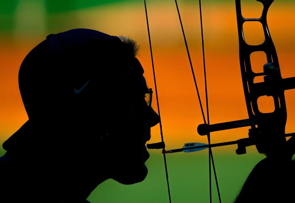 A disabled archer prepares to shoot by using his teeth to pull back the arrow.
