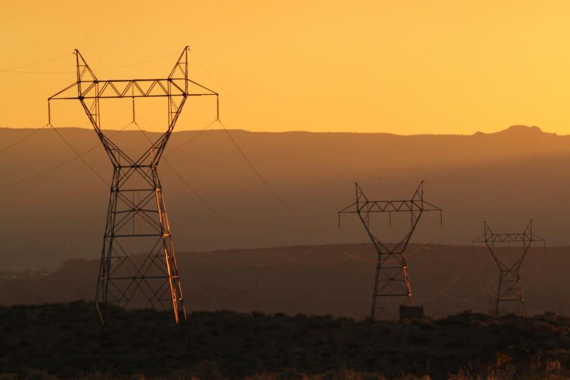 This Aug. 20, 2019, image shows transmission lines leading from the Navajo Generating Station near Page, Ariz. The power plant will close before the year ends. Other coal-fired plants in the region and in the U.S. are on track to shut down or reduce output as utilities turn to natural gas and renewable energy. (AP Photo/Susan Montoya Bryan)