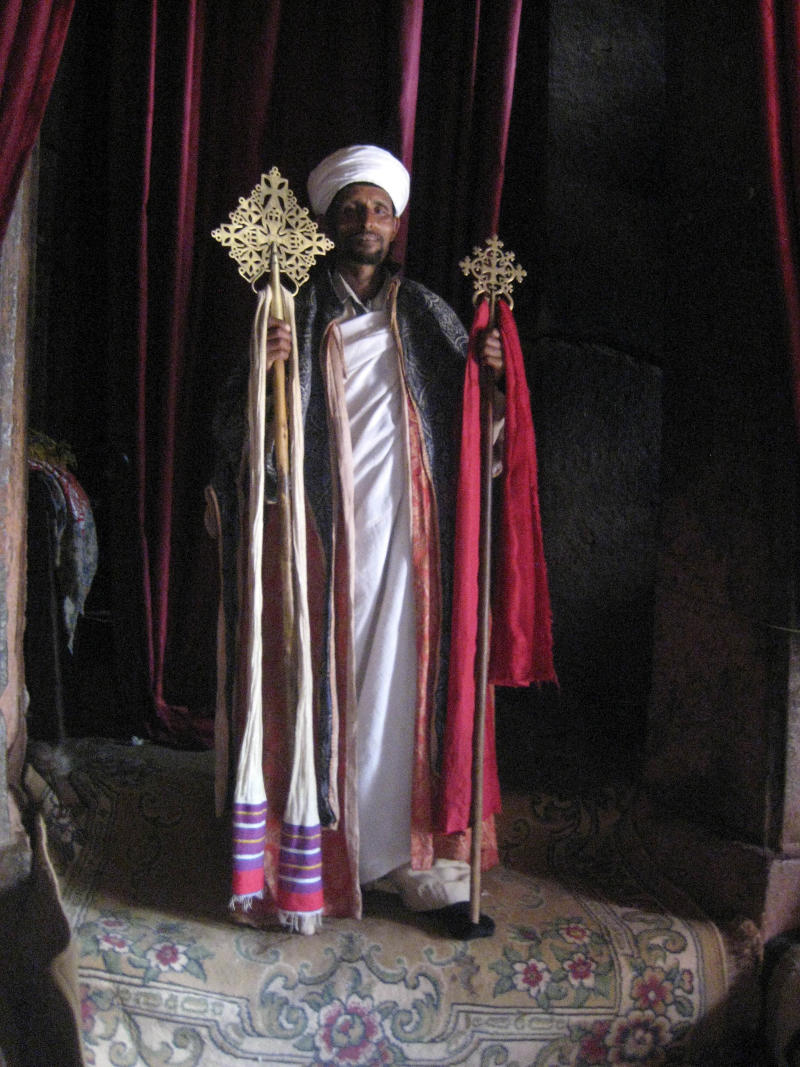 This April 2010 photo shows a priest inside a church at Lalibela, Ethiopia.  Lalibela has a winding complex of 11 churches cut out of the rust-red granite tucked into a wind-swept moonscape. Legend claims it's the work of angels but in reality the complex was commissioned by the powerful 12th-century King Lalibela and picked out of the rock with hammers and chisels over decades.    (AP Photo/Jenny Barchfield)