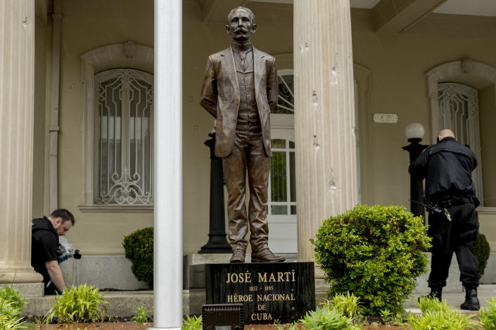 Bullet holes are visible on a column behind a statue of Cuban independence hero José Martí as Secret Service officers investigate after police say a person with an assault rifle opened fire at the Cuban Embassy, Thursday, April 30, 2020, in Washington. Officers found the suspect with an assault rifle and took the person into custody without incident, police said. (AP Photo/Andrew Harnik)