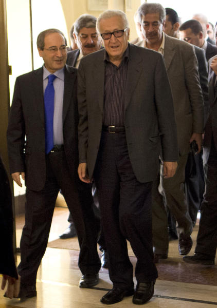 U.N.-Arab League envoy Lakhdar Brahimi, right, and Deputy Syrian Foreign Minister Faisal Mekdad arrive to a hotel surrounded by security Monday, Oct. 28, 2013 in Damascus, Syria. Brahimi is on his first trip to the country in almost a year. (AP Photo/Dusan Vranic)