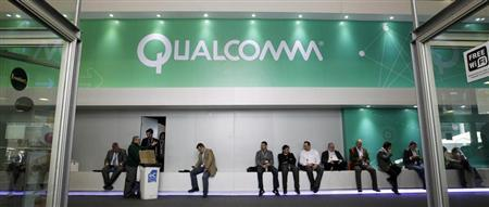 People sit next a Qualcomm stand at the Mobile World Congress at Barcelona