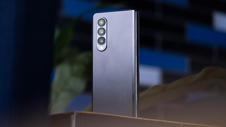 The Samsung Galaxy Z Fold 3 standing on a desk with its triple camera system facing the camera.