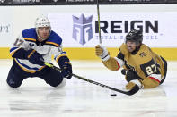 St. Louis Blues left wing Jaden Schwartz (17) and Vegas Golden Knights defenseman Shea Theodore (27) dive for the puck during the first period of an NHL hockey game Saturday, May 8, 2021, in Las Vegas. (AP Photo/David Becker)
