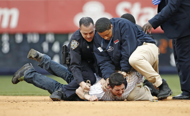 A police officer and a security officer tackle a fan who ran onto the field in the eighth inning of the Yankees 14-5 loss to the Baltimore Orioles during the MLB American League baseball game at Yankee Stadium in New York, Tuesday, April 8, 2014. Two fans made it onto the field behind second base and were tackled and escorted off the field as players watched. (AP Photo/Kathy Willens)