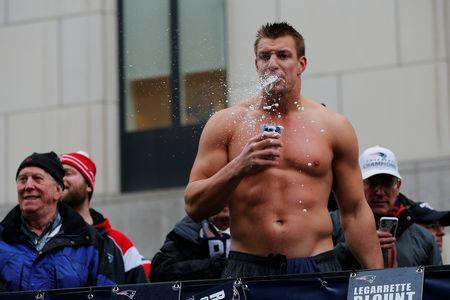 New England Patriots tight end Rob Gronkowski drinks a beer thrown to him from the crowd during the Patriots victory parade through the streets of Boston after winning Super Bowl LI, in Boston, Massachusetts, U.S. February 7, 2017. REUTERS/Brian Snyder