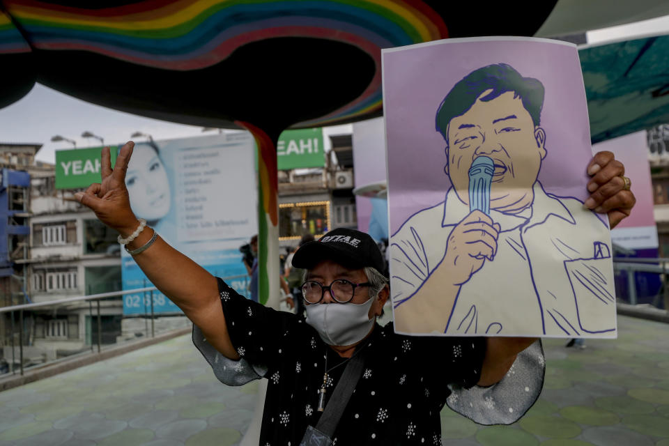 A pro-democracy protester flashes a three-fingered salute and displays an image of protest leader Parit Chiwarak during a protest in Bangkok, Thailand, Wednesday, Feb. 10, 2021. Prosecutors in Thailand on Tuesday charged four prominent pro-democracy activists, including Parit, with sedition and defaming the monarchy for their protest activities. (AP Photo/Sakchai Lalit)