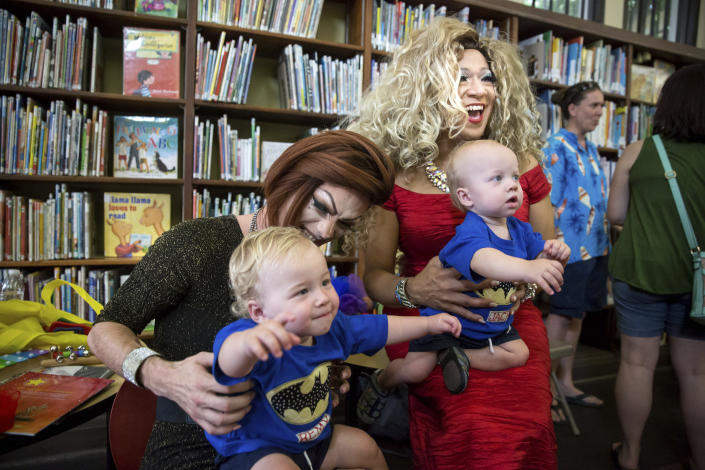 Blazen Haven, left, and Vanessa Carr meet twins Remy Karas, left, and Jack Karas, both 14 months, during Drag Queen Story Time at the Alvar Library in New Orleans on Saturday, Aug. 25, 2018. Children and parents and caregivers packed into the library to hear stories and sing songs during the event. (Scott Threlkeld/The Advocate via AP)