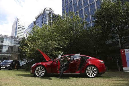 A visitor looks at a Tesla Model S electric car at the Motorexpo in Canary Wharf, London