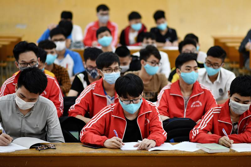 Students, wearing facemasks amid concerns of the COVID-19 novel coronavirus outbreak, attend a class at the University of Science and Technology campus in Hanoi on March 2, 2020. - (Photo by Manan VATSYAYANA / AFP) (Photo by MANAN VATSYAYANA/AFP via Getty Images)