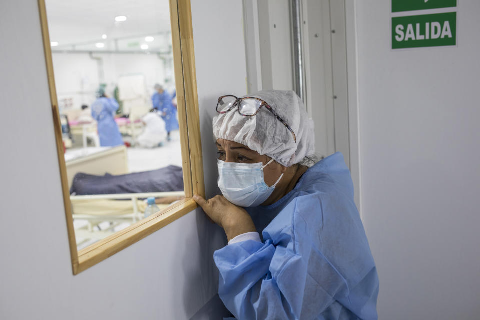 A woman watches as a relative infected with COVID-19 receives supplemental oxygen at the Regional Hospital in Iquitos, Peru, Monday, March 22, 2021. In April 2020, the pandemic hit Peru hard, and Iquitos was struggling with the area's only two hospitals lacking sufficient space to attend COVID-19 patients. (AP Photo/Rodrigo Abd)