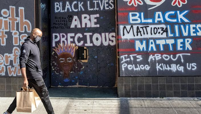 A person walks by a boarded-up shop in Oakland, California on February 12, 2021. - Racial minorities have borne the brunt of the Covid-19 pandemic in the United States, with higher rates of death, unemployment and business failure, and less success obtaining federal government assistance intended to provide relief. (Photo by JOSH EDELSON / AFP) (Photo by JOSH EDELSON/AFP via Getty Images)