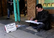 An unemployed man, Enrique, writes poems in return for a cash handout on the eve of the Spanish general elections on November 19, 2011 in the center of Madrid, Spain. (Photo by Jasper Juinen/Getty Images)