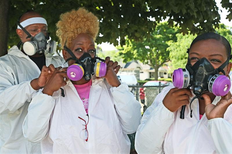 Jeffery B. Hardy Sr., from left, helps his wife Brenda, put on a respirator after assisting daughter Breanna Hardy with hers before entering the church.