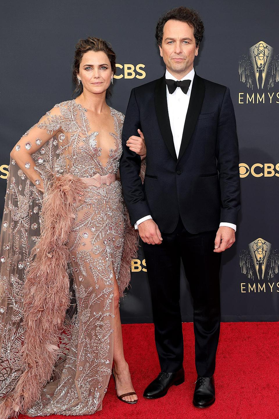 <p>The couple, who starred in <em>The Americans </em>together from 2014 to 2018, channeled Old Hollywood glamour with their red carpet looks. Rhys wore a classic black tux, which Russell pulled out all the stops in a sheer, sequined gown including feather sleeves. </p>