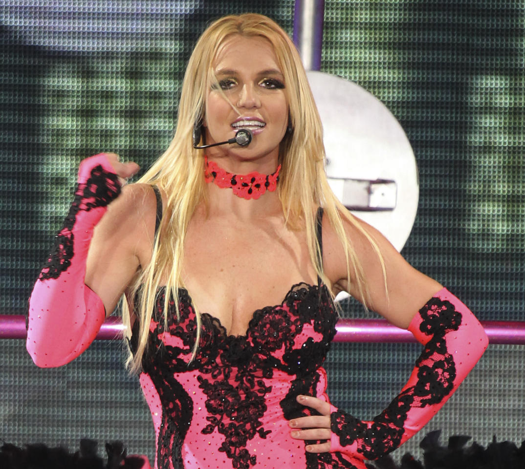 """FILE - In this Sept. 24, 2011 file photo, singer Britney Spears performs on a stage during a concert in Moscow, Russia, during her European tour.  A source says she is joining Simon Cowell's singing contest as a judge on the singing competition series """"The X-Factor."""" (AP Photo, file)"""