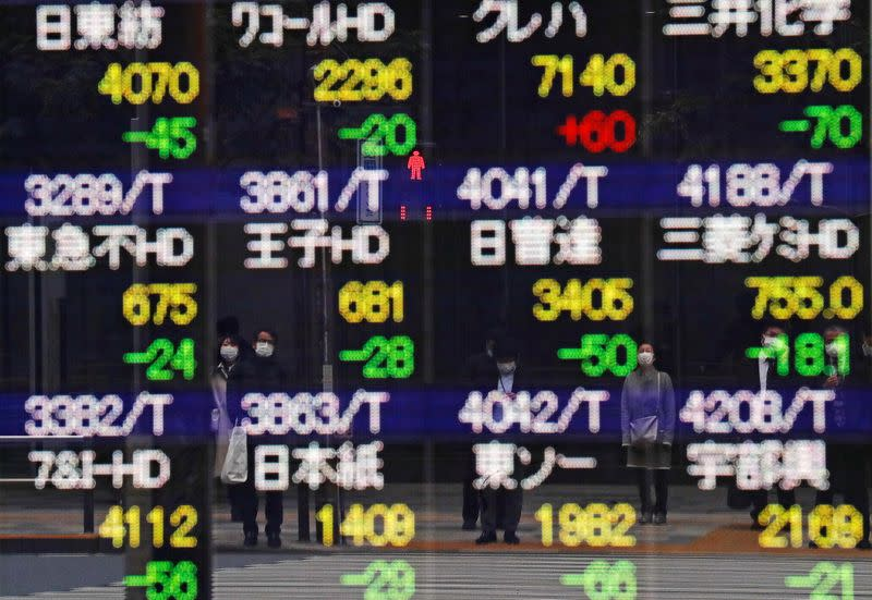 FILE PHOTO: Pedestrians and a traffic light stop sign are reflected on a quotation board in Tokyo