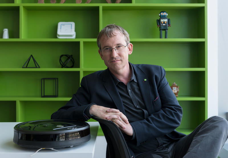 iRobot chairman, CEO, and co-founder Colin Angle sitting next to a Roomba with a green shelf in the background