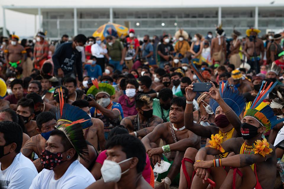 BRASILIA, BRAZIL - AUGUST 26:Indigenous people gather as they watch a demonstration to protect their land on August 26, 2021 in Brasilia, Brazil. Over 6,000 indigenous people gathered at a camp in Brasilia summoned by Articulação dos Povos Indígenas do Brasil and marched up to the Supreme Court to protest against a judgement which may define the demarcation of indigenous lands.The trial has been postponed to September 1st. (Photo by Andressa Anholete/Getty Images)